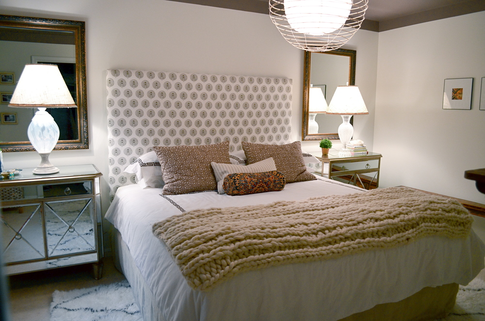 Symmetrically placed mirrored pieces enlarge the master bedroom.  A custom headboard gives a designer's touch to the inviting bed, layered with thoughtful patterns and textures.  An eclectic light fixture adds a touch of whimsy and unpredictability to an otherwise traditionally styled bedroom.