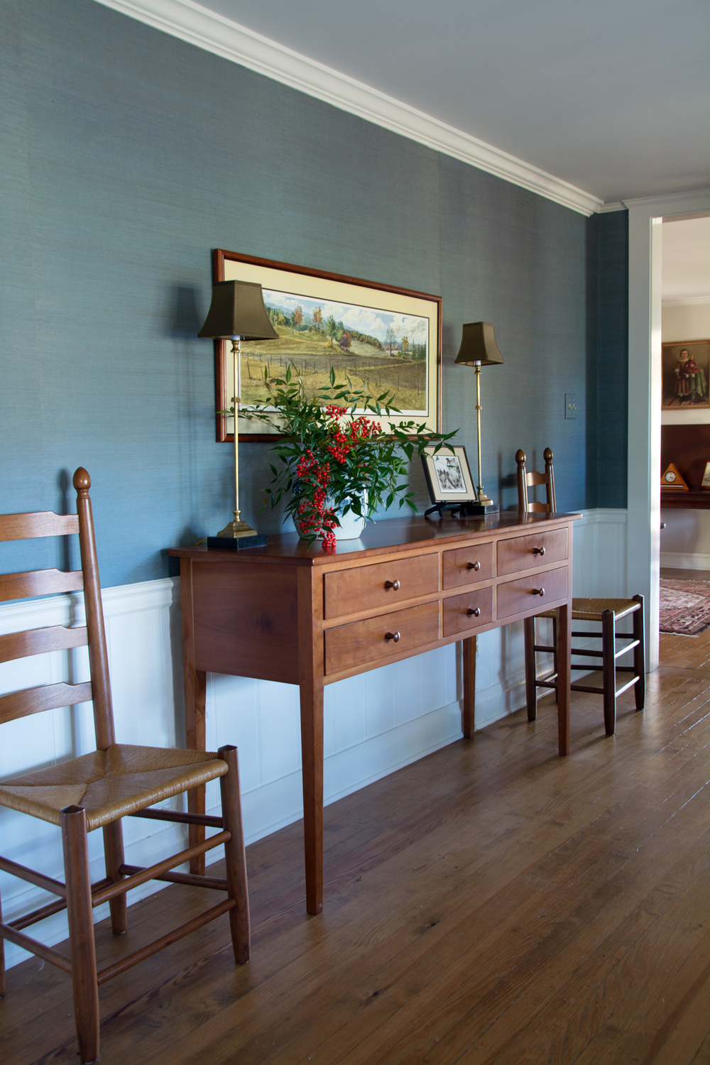Deep in the heart of Virginia horse country this equestrian farm client wanted to maintain her traditional style, while providing updated colors and accessories.  We added a rich blue grasscloth and buffet lamps and rearranged her art in this dining room.
