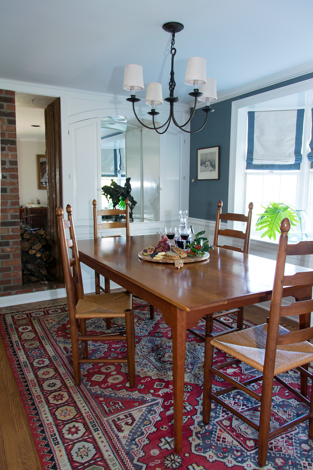 A colorful vintage kilim rug gave new life to the dining room.  New white trim and a painted built in cabinet was updated with a custom mirror in the niche.  Custom roman shades enhanced the bay window.