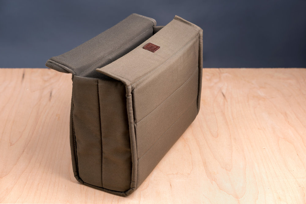 Wotancraft's shock-resistant  Quickdraw Insert  (with its proprietary dual flaps) surrounds your gear in a protective luxury.  It is removable and finished in a luxurious microfiber lining. The  Quickdraw   Insert  can also be interchanged for their  Waterproof Insert .