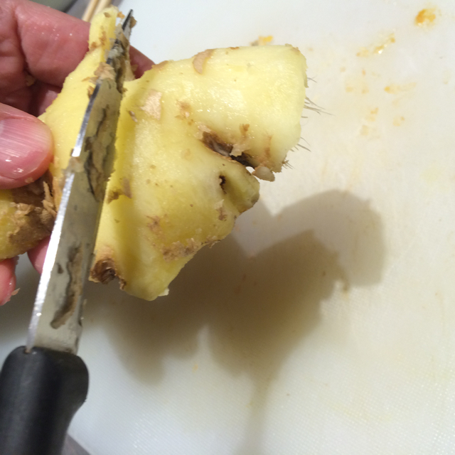Removing ginger skin with a knife
