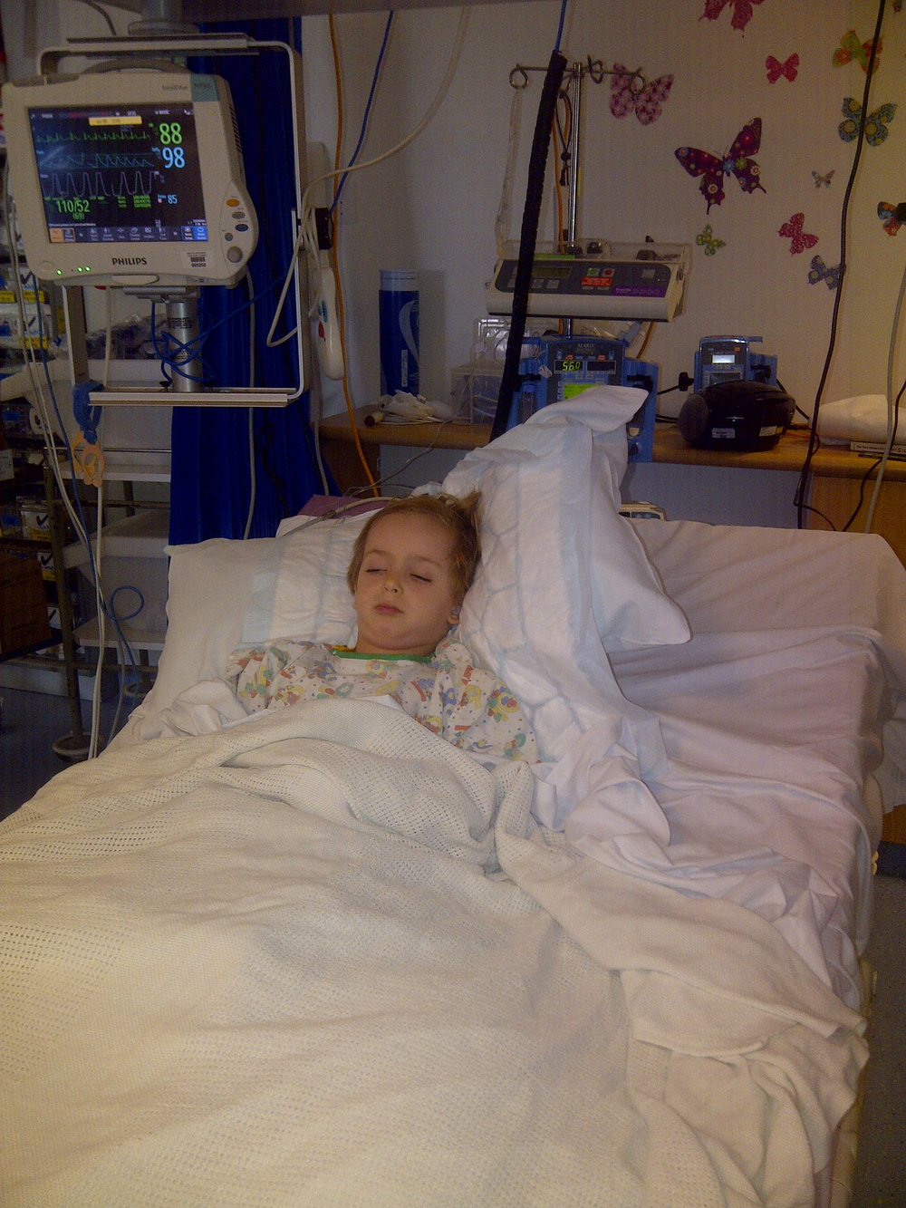 Skye lying in PICU post surgery