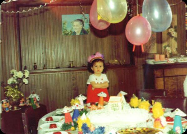 """Roxana Martinez   """"Mis dos o tres años celebrados en la casa de mis abuelitos. Todo listo, lassopresas de honguitos, mi vestido nuevo que me hizo mi mamáy yo furiosaporque nada que llegaban los invitados.Al fondo retrato de mi bisabuela."""""""