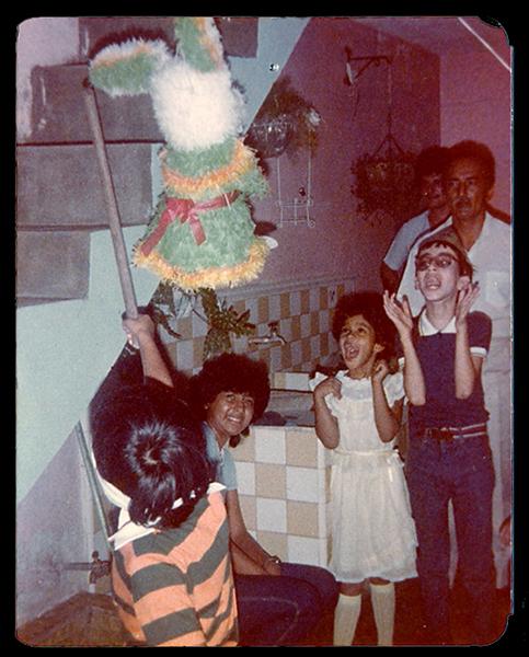 """Diana Marcela Cuartas    """"Me he tomado el atrevimiento de enviarles esta fotico, tomada en un cumpleaños celebrado en Santiago de Cali. Qué pena lo terca, uds. podrán haberse planteado desde un principio como un proyecto de rolos para rolos pero por acá se les quiere entonces les toca aguantarse a uno que otro metiche, La fotito esta es de un cumpleaÒos celebrado en 1986 en un barrio de Cali que se llama precisamente El Popular, el agasajado es el chico del palo y la venda, pero quién se llevó toda la atención fue el jovencito del efusivo aplauso; muy folclóricos nosotros, nadie se pudo resistir a los encantos de un niño con ligero retardo mental pero un agudo sentido del humor. Este tiene ahora como unos 30 años, hace maletines por encargo y parece que la pasa muy bien. El otro mancito, el cumpleañero, por el contrario parece inconforme con la vida, es un poco más joven pero no ha tenido mucha fortuna con las mujeres y su experiencia laboral se compone de años y años atendiendo la tienda de su mamá en El Popular. La niña si ni idea, dejémoslo en que podría ser una versión femenina y mini de Nerón Navarrete ó por el aspecto de su cabello podrÌa ser la Momo de Michel Ende. Los adultos son María, mi abuelo Arturo y al fondo mi padrino José."""""""