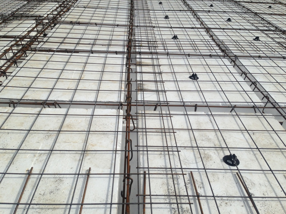 Reinforcing steel is laid both over the waffle pods and between the ribs.
