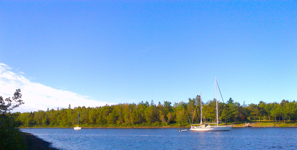 Peregrinus  safely anchored in   Halcyon Cove, inside Cumberland Bay, Grand Lake.  The Zodiac hangs from  Peregrinus'  stern and Garry's  Happenstance  lies on a mooring deeper inside the cove.  BlackBerry 9900, 7 September 2014.