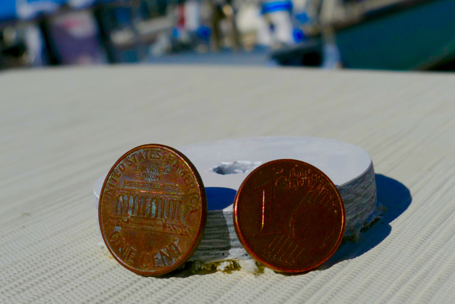 1¢ U.S. dollar and 1¢ Euro and the hull cutout.  The hull is thicker at the waterline and below, and fibreglass is a hardy material, but it is still unnerving to contemplate what separates one from the great blue out there.  Leica Typ 114, 10 July 2015.