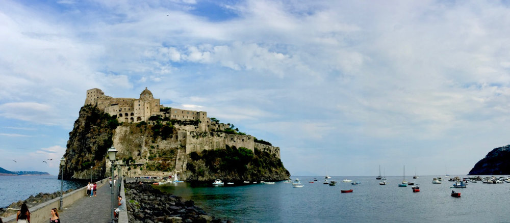The Aragonese Castle at Ischia, with  Peregrinus  visible at anchor in the artificial bay created by the causeway built by King Alfonso V of Aragon, Naples, Sicily and diverse others, and uncle of King Ferdinand the Catholic, he who sent Columbus looking for the Indies.  9 September 2016, iPhone 6 Plus.