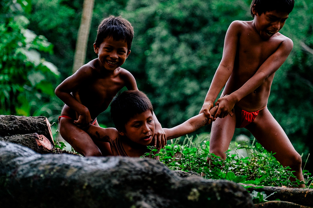 Three Embera children are play fighting by the river. It is comforting to see the children of the village finding ways to have fun without technology, play fighting, playing tag and even drawing games on the ground with rocks. This brings back nostalgic feelings from my childhood before technology really took hold of our lives.