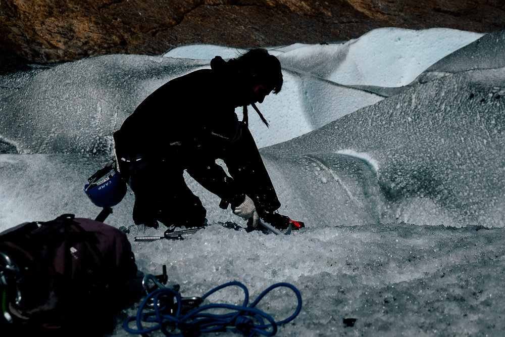 Drilling the cable stays into the ice to set up the anchors for the rope.