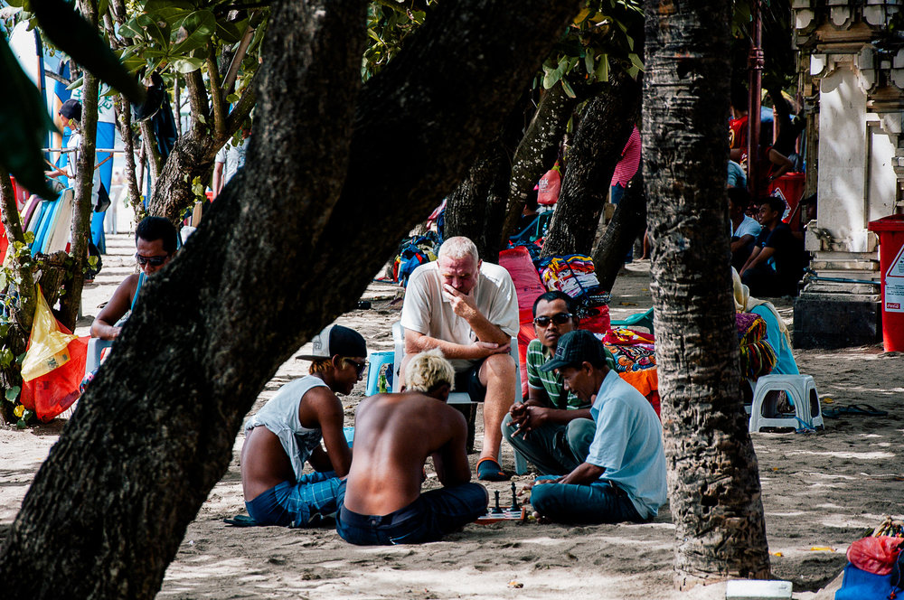 Tourist playing chess with some of the locals on the beach.