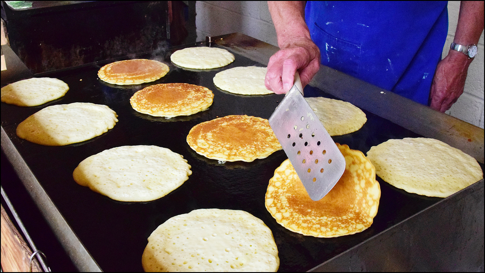 just a photo of a guy flipping pancakes on a griddle (c) mark somple 2018