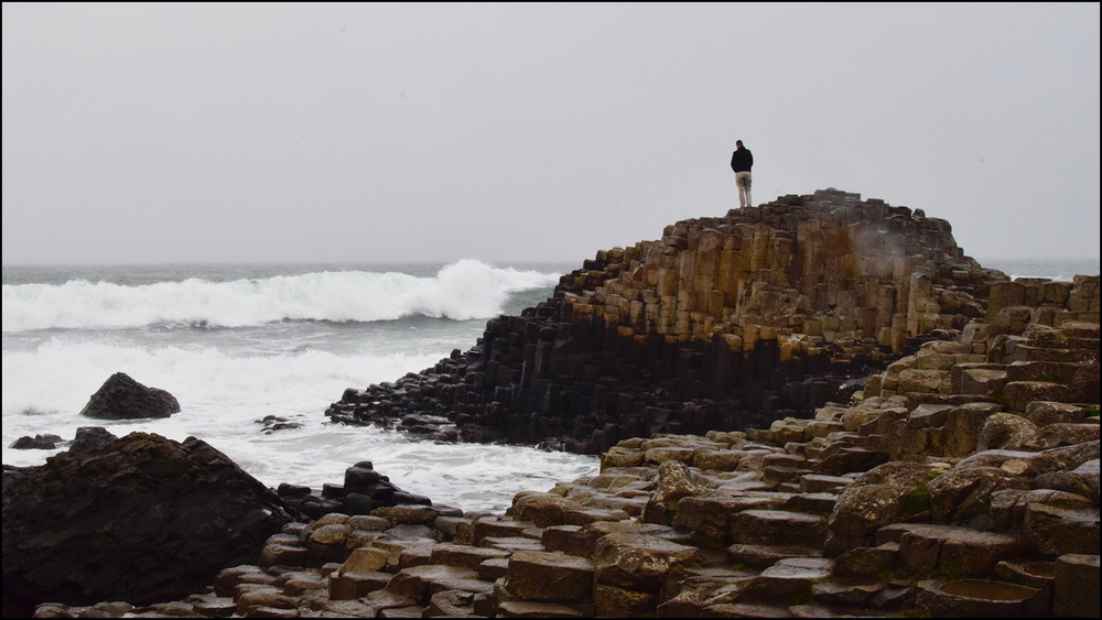 man taking a moment to ponder life upon the unique stones that are giants causeway (c) mark somple 2019