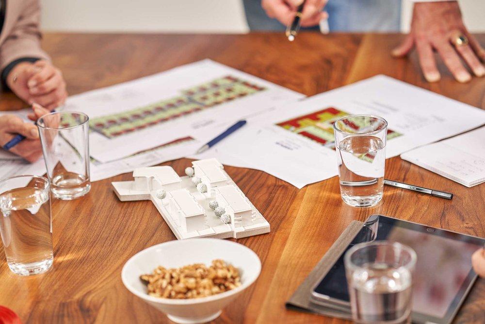 Präsentationen und Pläne liegen auf dem Tisch. Es wird über neue Planungen gesprochen.
