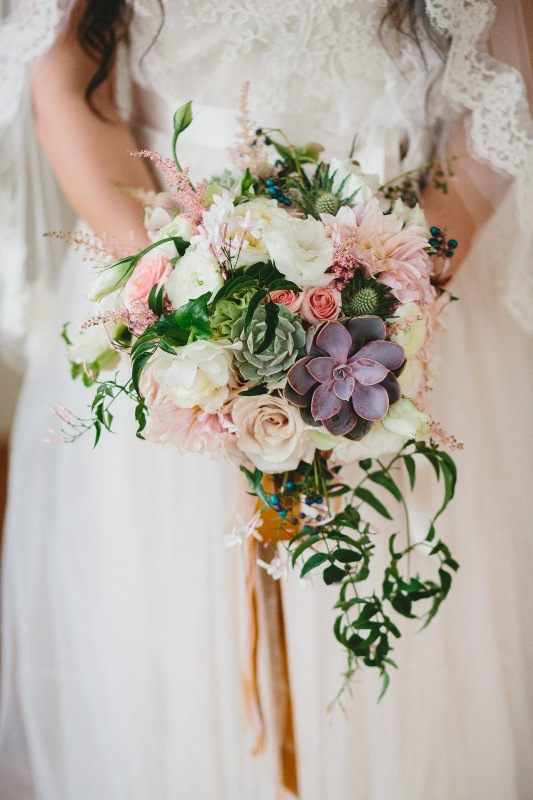 Ashley's stunning bouquet was created with Cafe Au Lait Dahlias, Lisianthus, Succulents, Quicksand Roses, Hellebores, Eryngium, Astilble, Jasmine vine, and Porcelain berries vine. With vintage ribbons and trims.