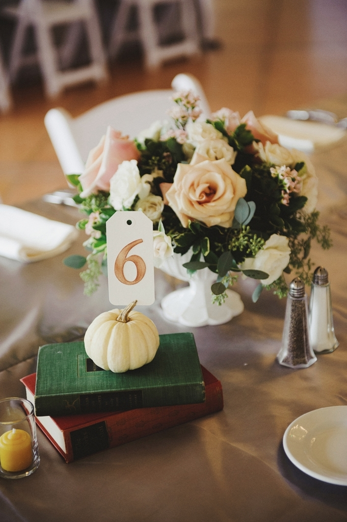 Surrounded by classic hardcover books, Fall votives, and a few small ivory gourds, the centerpieces consisted of Mother of Pearl Roses, White Majolika Spray Roses, Seeded Eucalyptus, Variegated Pitt, and Ariella Footed Compotes.