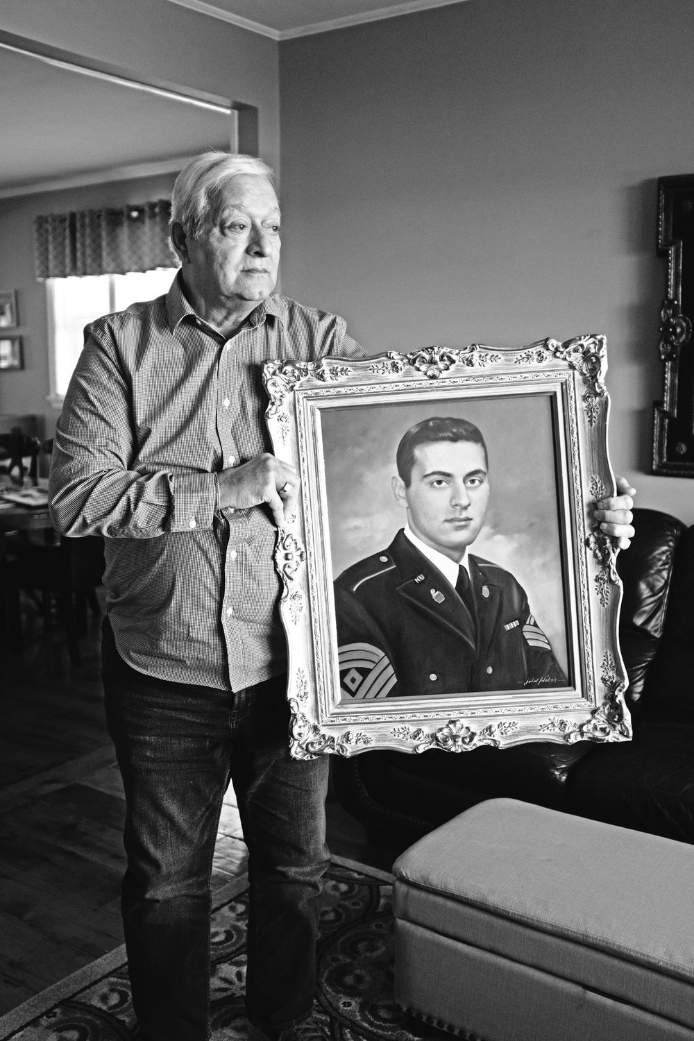 Tony D'Amico with a painting of his brother, Frank, which hangs in his bedroom. He and his siblings had the portrait painted following Frank's death as a gift to their parents. (Photograph by Thi Linh Wernau)