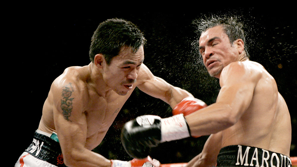 Manny Pacquiao, left, deals a crushing blow to Juan Manuel Marquez, right.
