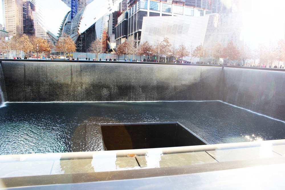 Two remembrance pools sitting in the plaza. The museum can be seen in the background along with a new pavilion currently under construction.