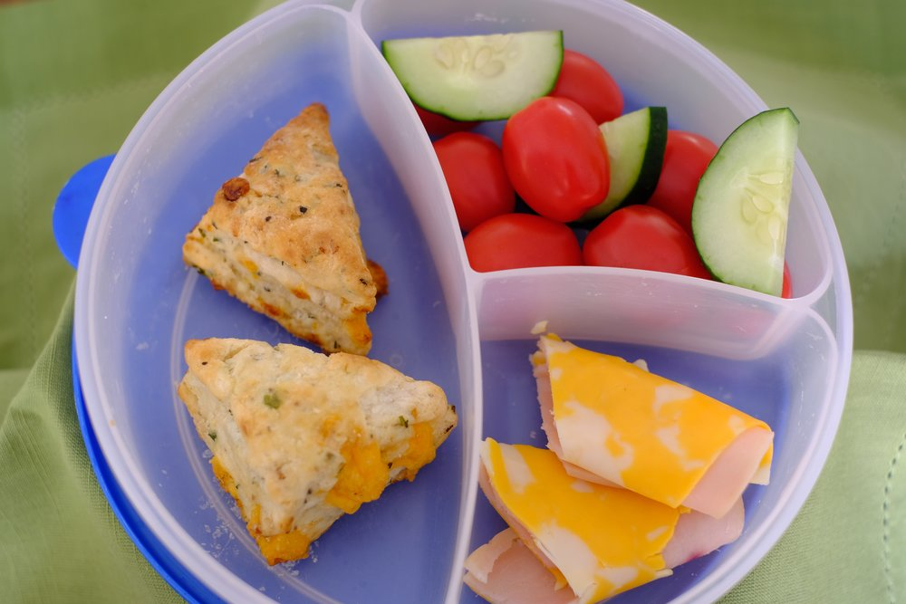 Bacon Cheddar scones taste perfect with tomatoes and cucumbers plus a little ham and cheese roll.