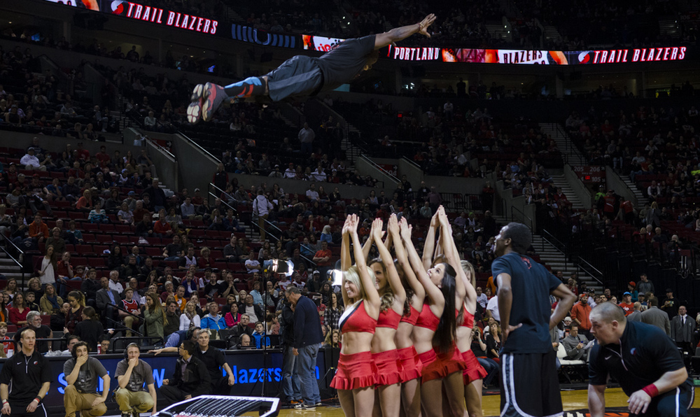 The creator of Mile HIgh Tumblers, Ozell Williams, glides over six Blazers Dancers during a halftime performance at a Portland Trailblazers game in March 2014.