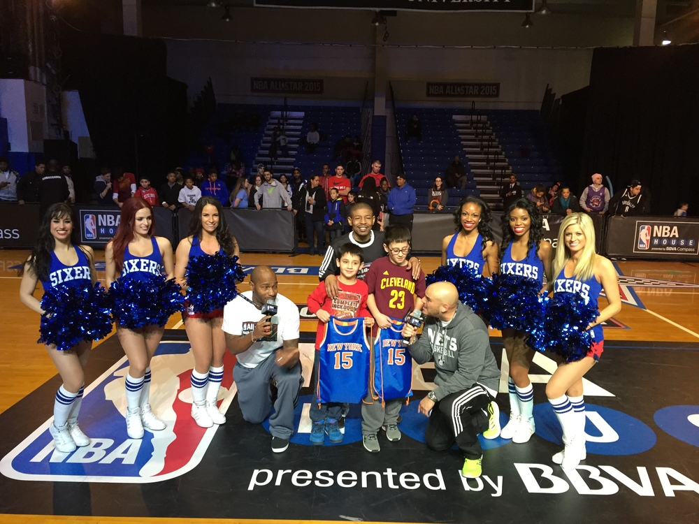 The Sixers Dancers, event emcees Wil Monestime & Miguel Batista and NBA Legend Muggsy Bogues pose with two contest winners at NBA House Brooklyn.