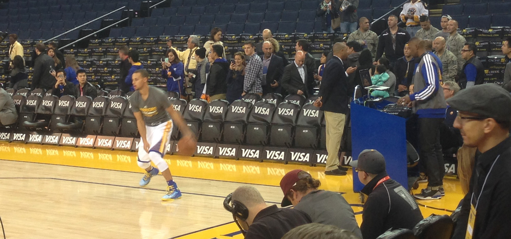 DJ D-Sharp (right) mixing for Warriors fans pre-game as Stephen Curry warms-up during shoot around.