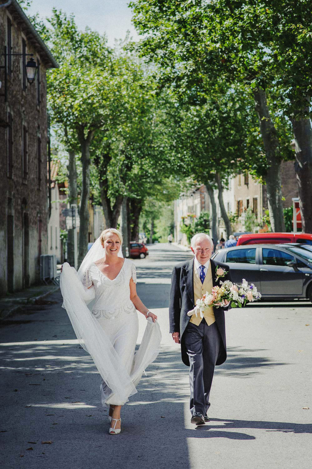 bride and father walking through french village