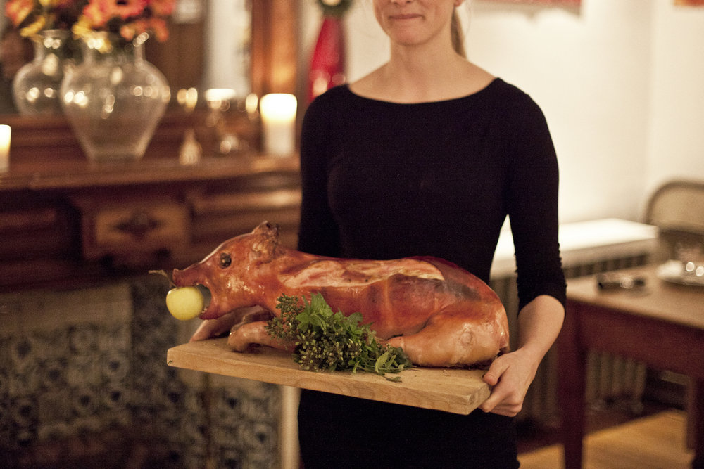 Young blonde woman holding a whole roast pig on a wooden cutting board at an Edible History 15th century italian feast.jpg