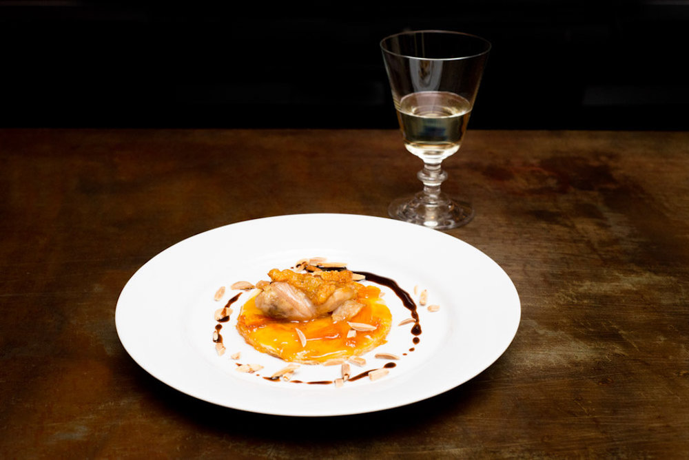 Gourmet dish with glass of wine on wooden table.jpg