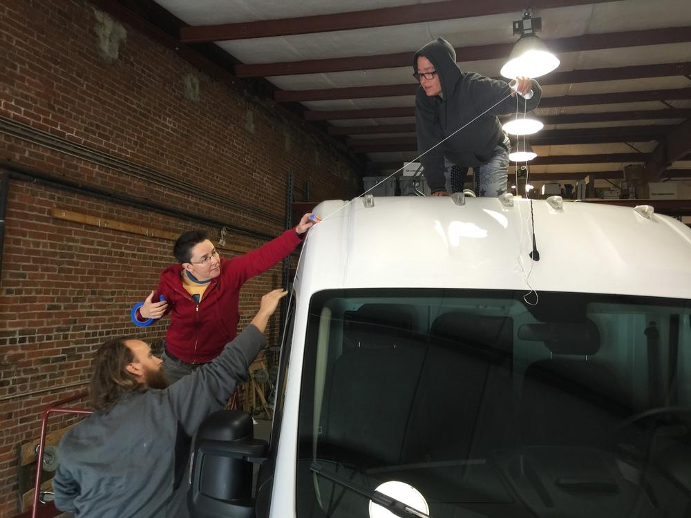 Artist Heather Gordon (top) and assistants begin installation of art project on Kontek Van