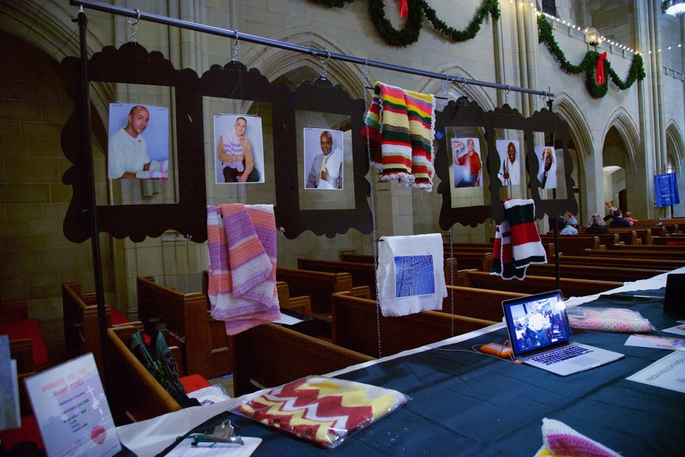A DISPLAY OF MEN WHO CROCHET IN PRISON AND A SAMPLE OF THE BABY BLANKETS THEY MADE