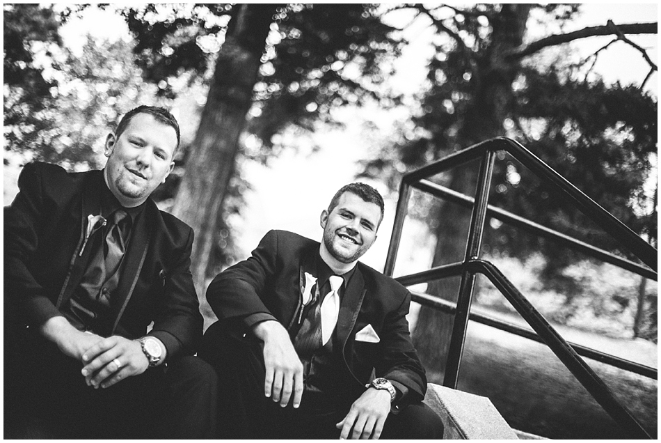 Groom and best man sitting on the steps - black and white
