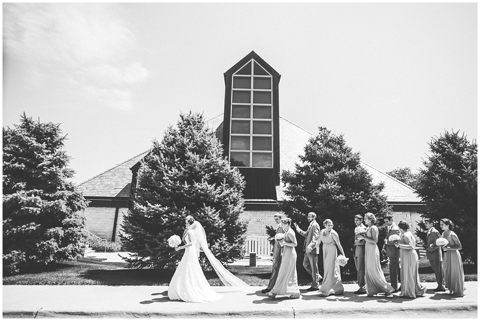 wedding party walking in front of church