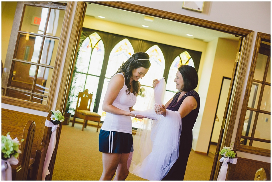 Bride and her mom looking at handmade veil