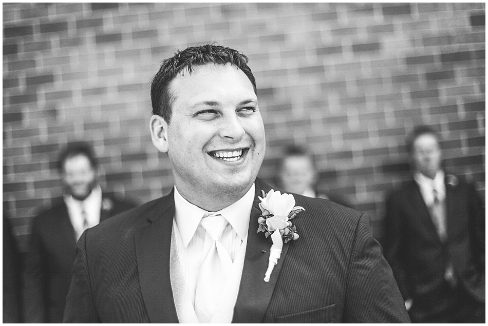 Groom laughing and looking off camera in black and white