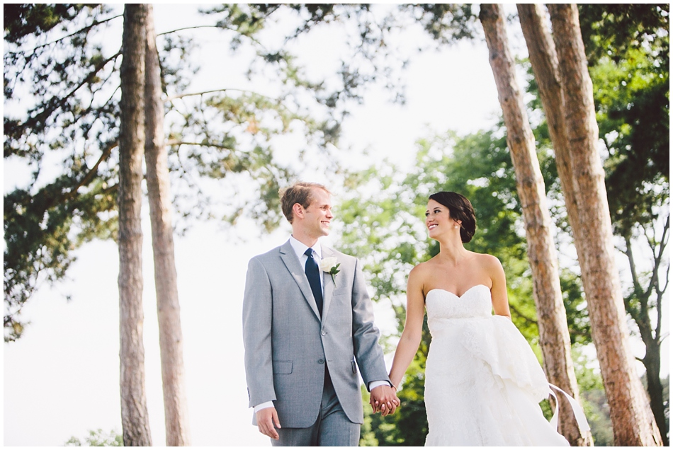 Bride and groom walking and looking at each other on golf course cart path