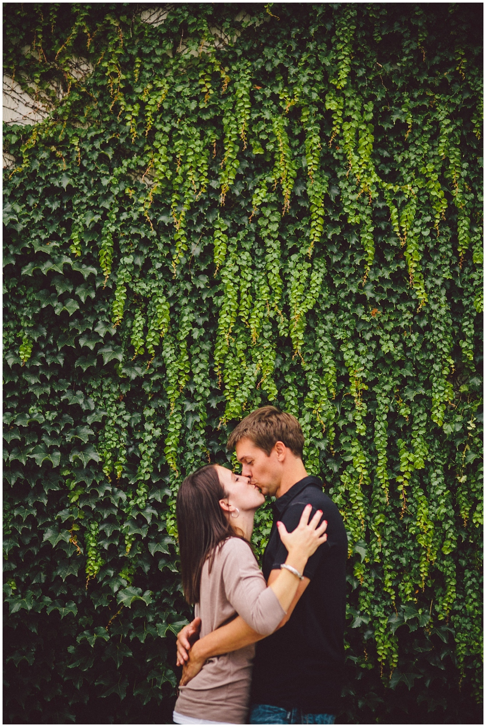 engaged couple kissing in front of green ivy wall