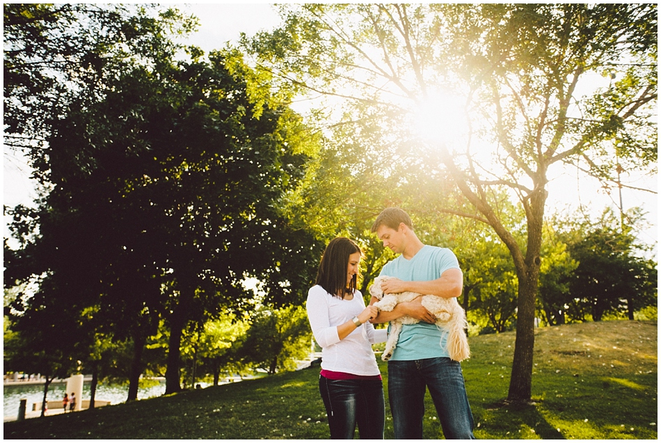 Backlit photo with couple playing with dog