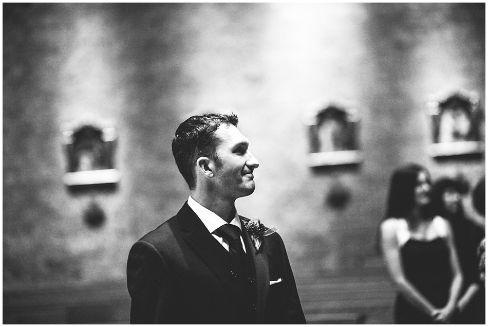Groom looking at bride when walking down the aisle