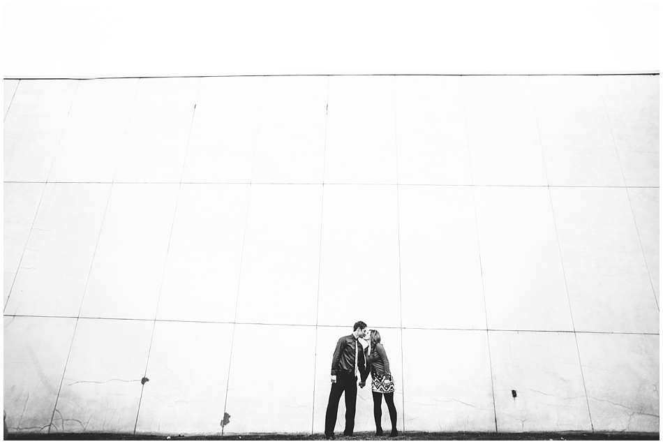 couple kissing in front of wall