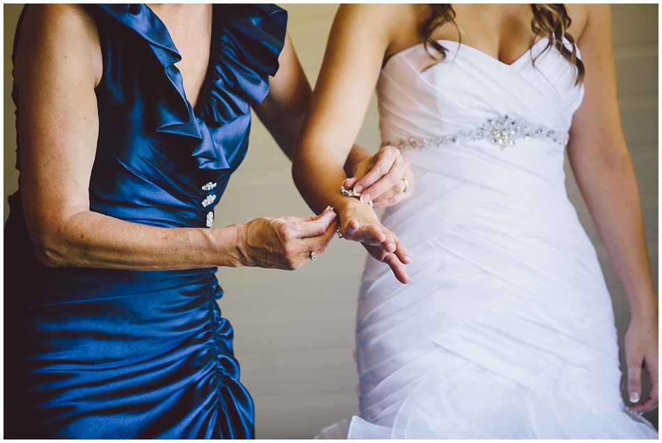mom putting on bride's bracelet
