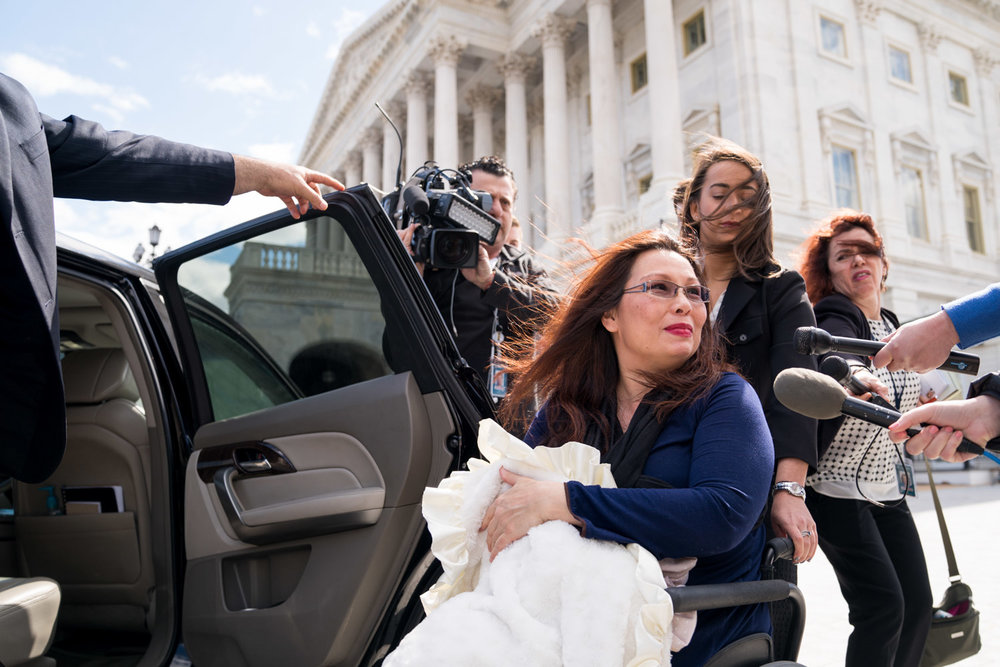 "Senator Tammy Duckworth (D-IL), holds her 10-day-old daughter Maile while talking with reporters outside the Capitol after a vote in Washington, DC on April 19, 2018. In an historic change of Senate rules, the lawmakers voted to allow infants of members onto the floor for votes. ""It's about time,"" Duckworth said. (Erin Schaff for The New York Times)"