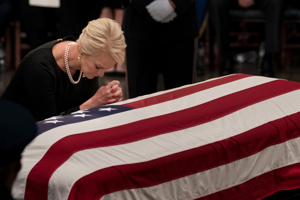 Cindy McCain, wife of the late Sen. John McCain, prays on the senator's coffin during a ceremony honoring him in the Rotunda of the U.S. Capitol, in Washington, DC on August 31, 2018. (Photo for The New York Times)
