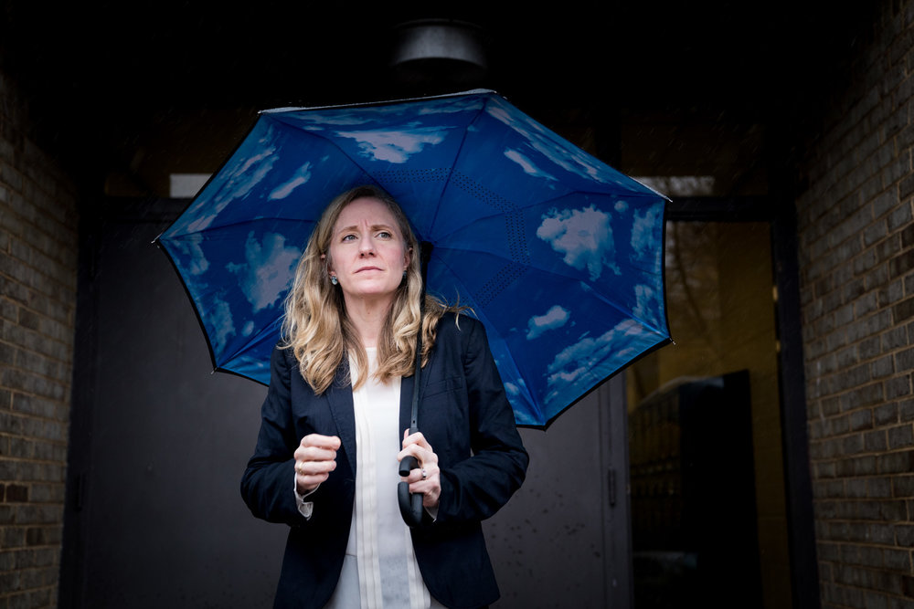 Abigail Spanberger, a Democrat running for congress in Virginia's 7th District, stands under an awning in the rain waiting to greet voters outside a polling location at Robious Middle School in Midlothian, VA on November 6, 2018. There was concern that the rain would lower Democratic voter turnout.