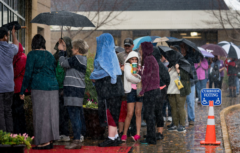 Over 100 people wait outside in the rain to vote at Robious Middle School in Midlothian, VA on November 6, 2018.