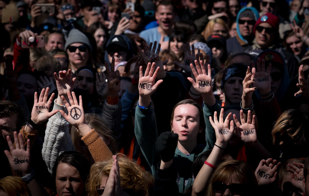 """People hold up their with """"never again"""" written in marker as part of a large crowd at the March for Our Lives rally, in Washington, DC on March 24, 2018."""