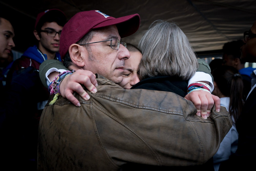 """Emma Gonzalez hugs her parents after speaking at the March for Our Lives rally in Washington, March 24, 2018. After reading the names of her slain classmates, Gonzalez remained silent for most of the six minutes and 20 seconds she was on stage. """"Fight for your life before it's somebody else's job,"""" she told the vast crowd."""