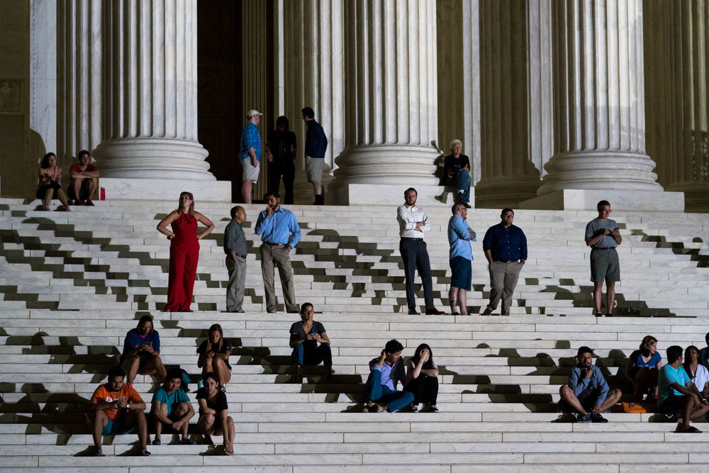 People watch a protest against Judge Brett Kavanaugh, President Donald Trump's nominee to the Supreme Court, from the steps of the Supreme Court just after the President announced Judge Kavanaugh as his nominee in Washington, DC on July 9, 2018.