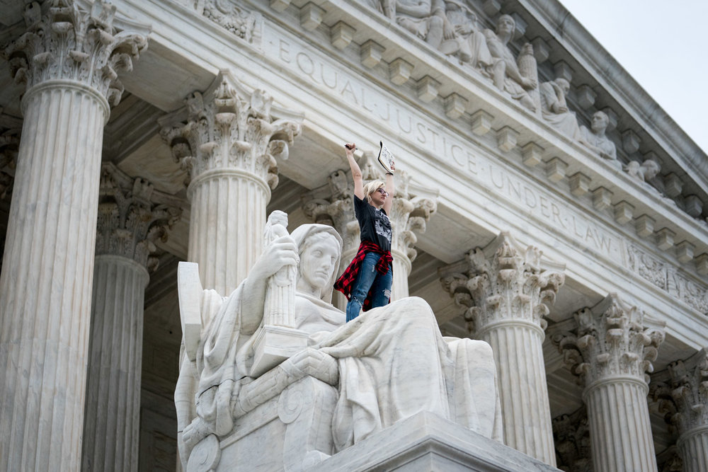 Jessica Campbell-Swanson, from Denver, stands on a statue titled the Contemplation of Justice outside the Supreme Court during a protest against Judge Brett Kavanaugh just after the Senate voted to confirm the Judge to the Supreme Court in Washington, DC on October 6, 2018.